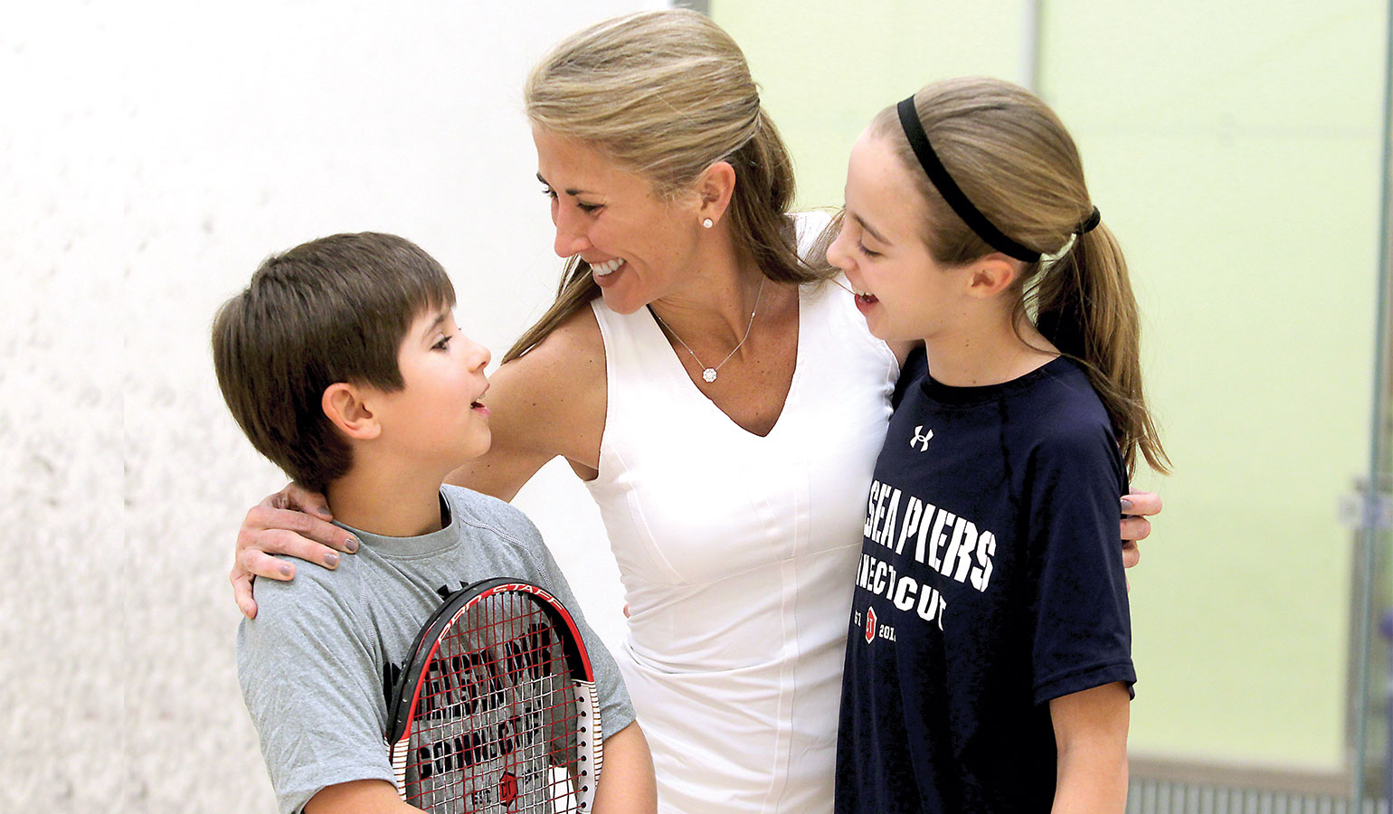 Family hugging after a squash match at Chelsea Piers